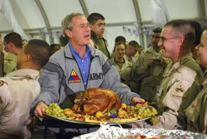 U.S. President George W. Bush carries a platter of turkey and fixings as he visits U.S. troops for Thanksgiving at Baghdad International Airport, November 27, 2003. Bush secretly traveled to Baghdad and paid the surprise Thanksgiving Day visit in a bold mission to boost the morale of forces in Iraq amid mounting casualties. REUTERS/Anja Niedringhaus, Pool EL NIE/SV